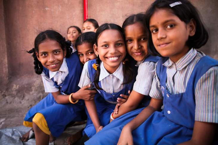 international day of the girl, group of school girls sitting together smiling