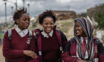 Three African school girls laughing