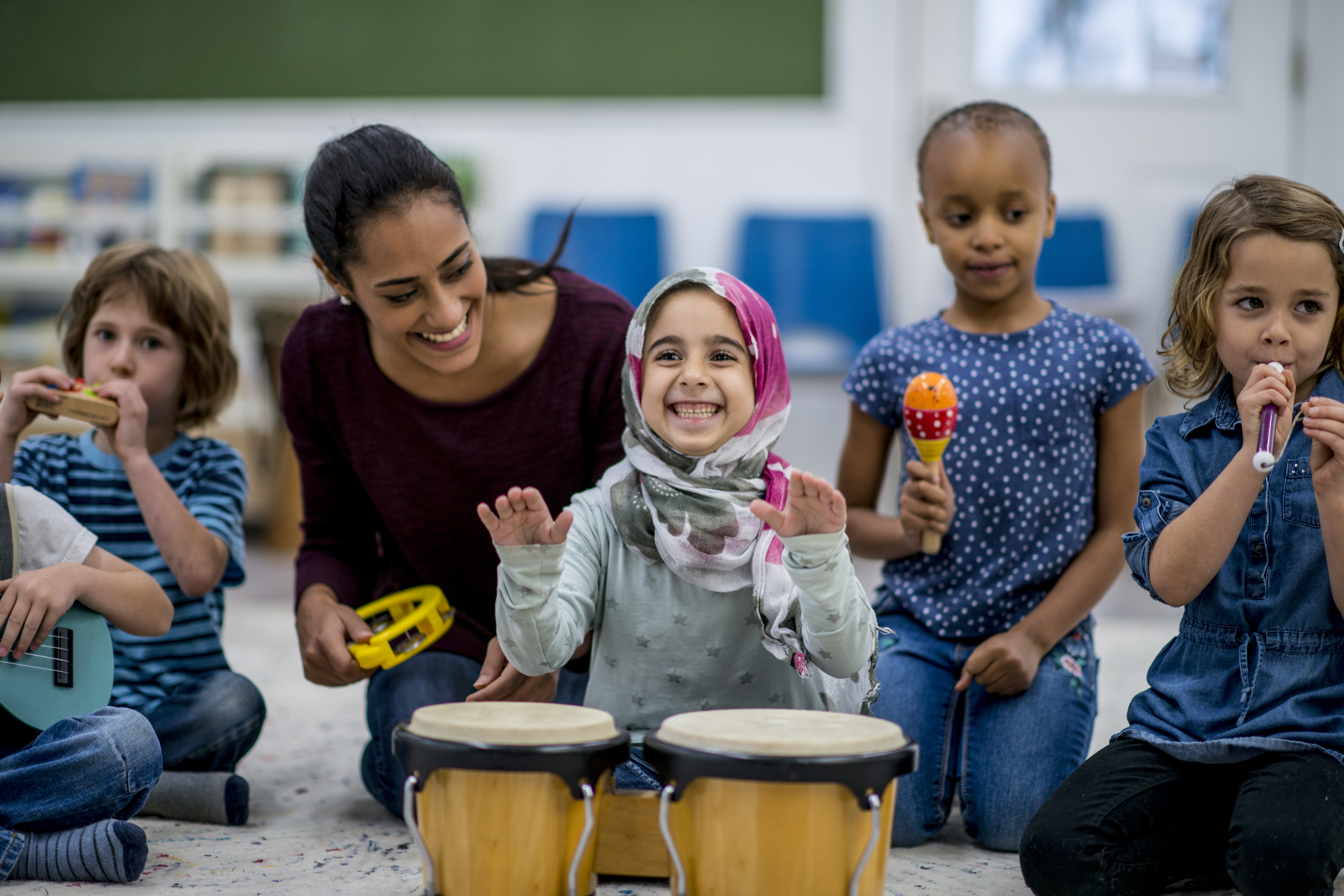 Playing Instruments: A multi-ethnic group of young school children are indoors in their classroom. Their teacher is watching them playing instruments together. The instruments include drums, maracas, and a guitar.