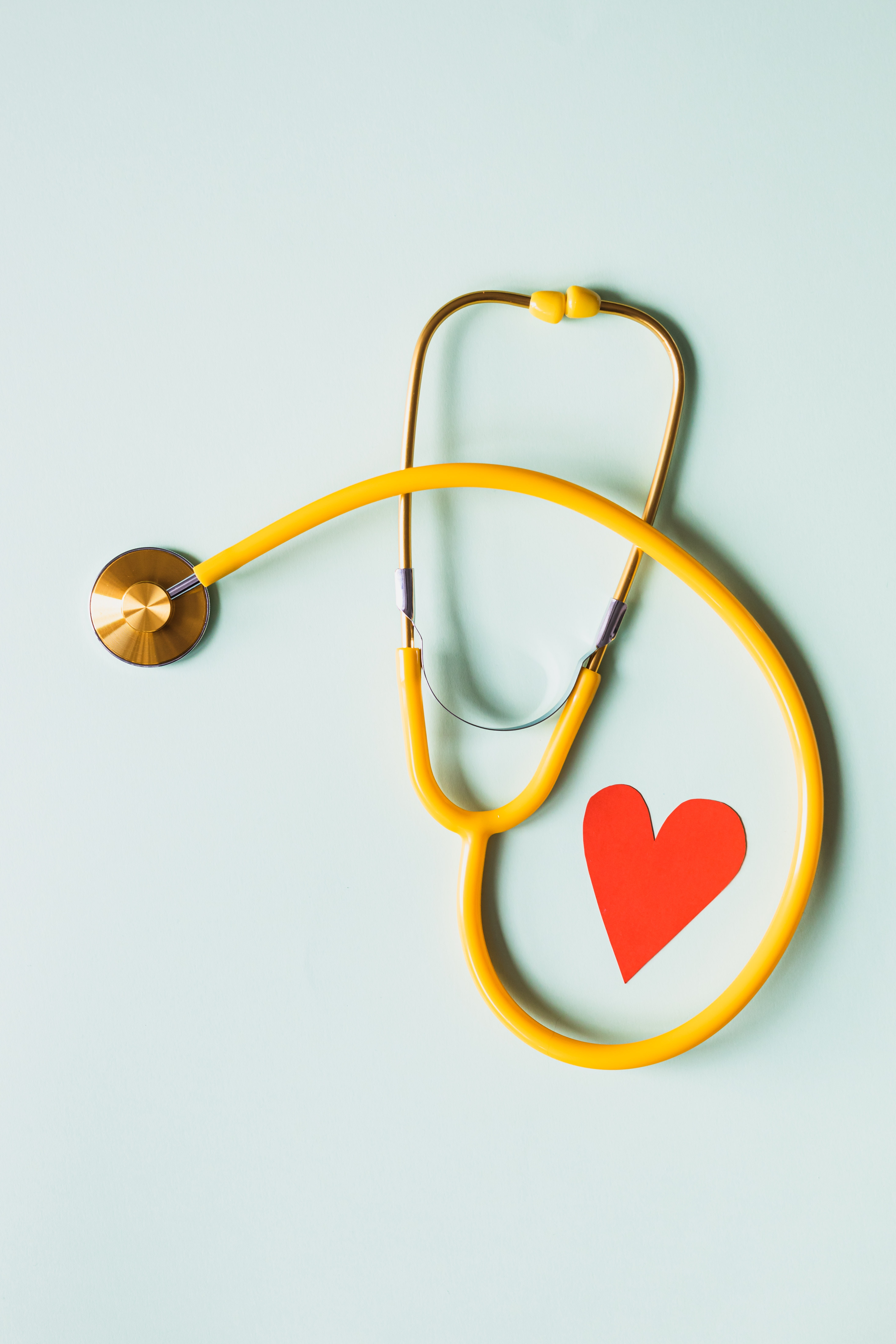 yellow stethoscope with paper heart