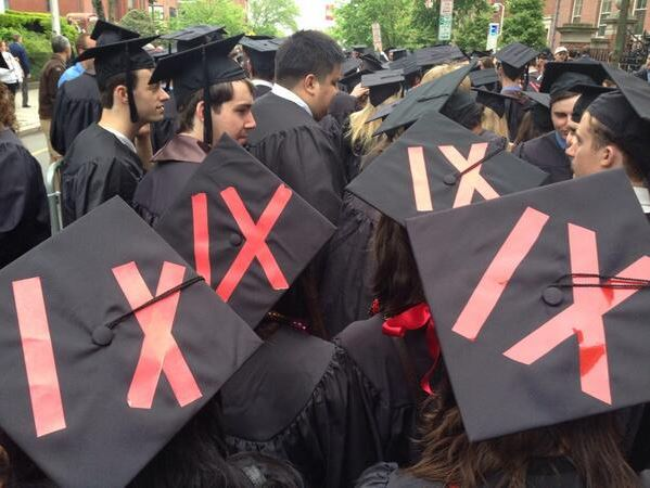 Students with graduation caps featuring Title IX in red lettering